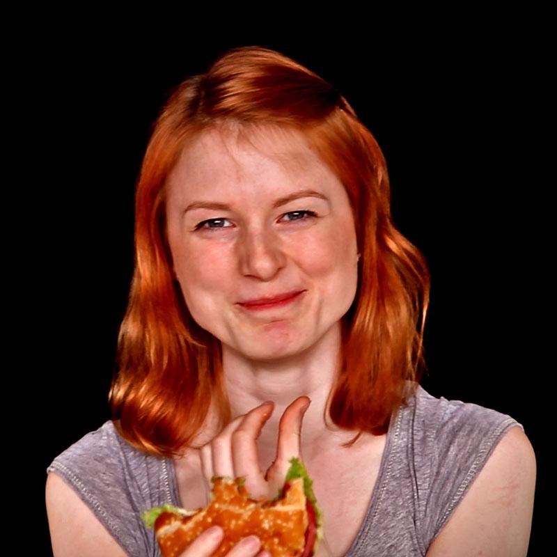 Eine junge Frau mit roten Haaren grinst in die Kamera. Sie hat gerade von einem Burger abgebissen, den sie in einer Hand hält.