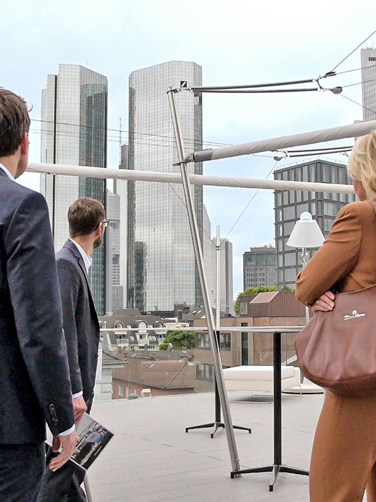Ausschnitt aus dem Eventfilm: Mehrere Personen stehen auf einer Dachterrasse, den Rücken zur Kamera gewandt, den Blick auf die Frankfurter Skyline gerichtet.