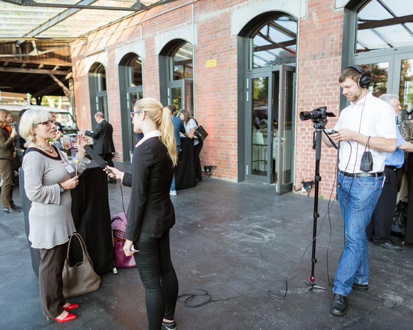 Ein Interview wird aufgenommen. Zur Rechten eine Person mit Kamera und Stativ, Kopfhörer sind aufgesetzt. Zur Linken zwei Frauen. Eine mit Mikrofon in der Hand, die andere antwortet mit Blick auf die erste Frau.