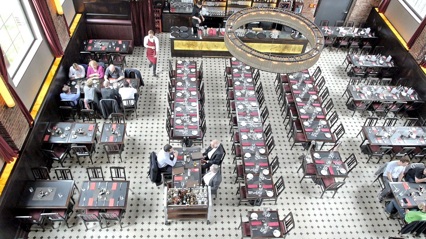 Blick von oben in ein Restaurant: Große Tische, viele Stühle, große Lampe. Das Wasserwerk in Frankfurt wurde auch mit der Kamera dokumentiert.