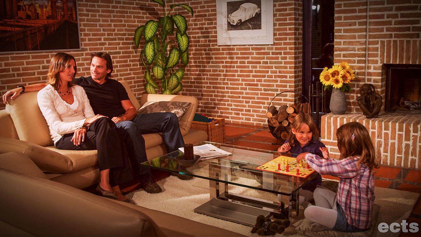Ein warmes geräumiges Wohnzimmer, die Wände bestehen aus Ziegeln. Eine Familie hat es sich gemütlich gemacht: das Ehepaar sitzt auf einer Couch und beobachtet die beiden Kinder, die miteinander spielen