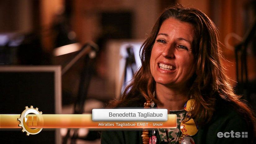 Standbild aus der Filmproduktion für den ECTS: Die Architektin Benedetta Tagliabue im Interview. Sie sitzt in einem Büro und lächelt symapthisch