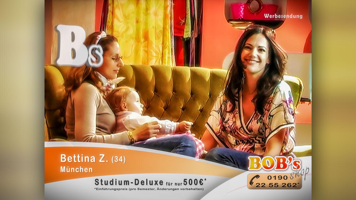 Szene aus dem Kurzfilm Studium-Deluxe: Die Schauspielerin Bettina Zimmermann sitzt auf einer gepolsterten Couch und lächelt in die Kamera. Neben ihr sitzt eine Frau mit einem kleinen Baby auf dem Schoß.