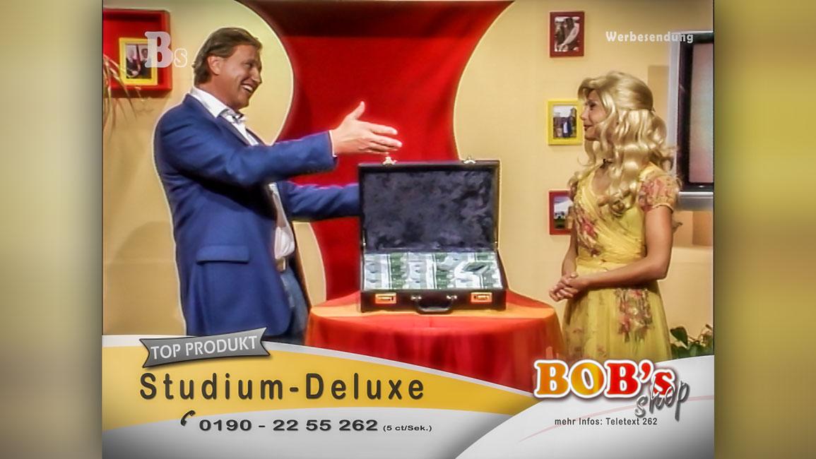 Zwei Verkäufer einer Televerkaufshow stehen sich grinsend gegenüber und unterhalten sich. Zwischen beiden steht auf einem Tisch ein geöffneter Koffer voller 100 Euro Scheine. Szenebild aus dem Kurzfilm