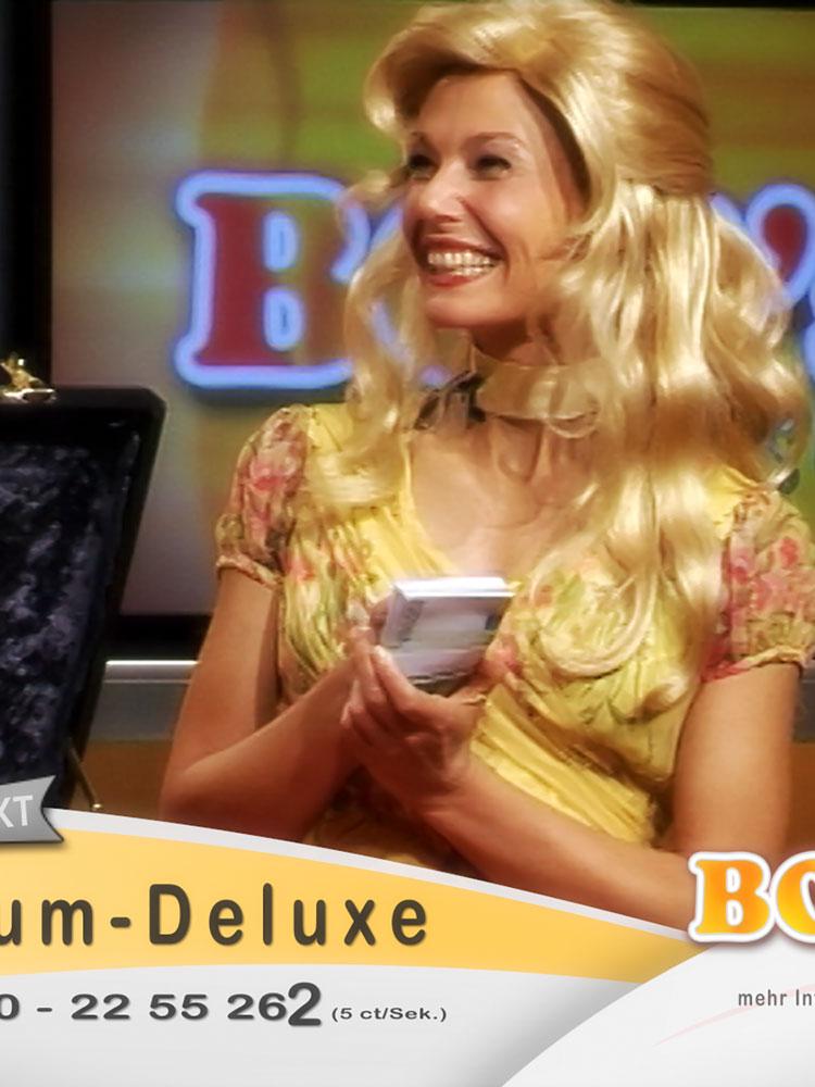 Eine Frau mit langen blonden Haaren hält ein Bündel Geldscheine in ihrer Hand und schaut grinsend links aus dem Bild heraus. Die Bauchbinde des Kurzfilms ist unten angeschnitten.