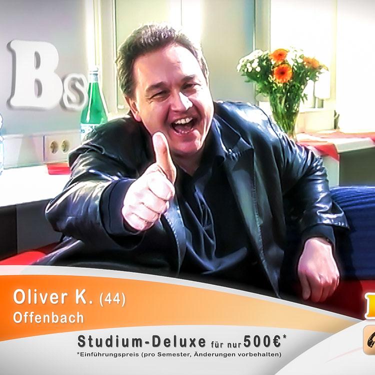Szene aus dem Kurzfilm Studium-Deluxe: Der Comedian Oliver Kalkofe sitzt auf einer Couch, blickt grinsend in die Kamera und reckt seinen Daumen in die Höhe.
