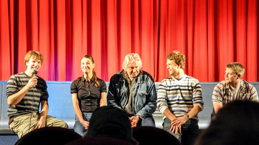 Regisseur Florian Thomi zusammen mit den Hauptdarstellern auf einer Bühne im Anschluss zur Premiere des Kurzfilms Studium-Deluxe