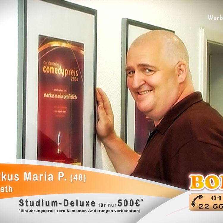 Der Comedian Markus Maria Profitlich steht vor einer Wand mit seinen Comedy Preisen und grinst überrascht in die Kamera