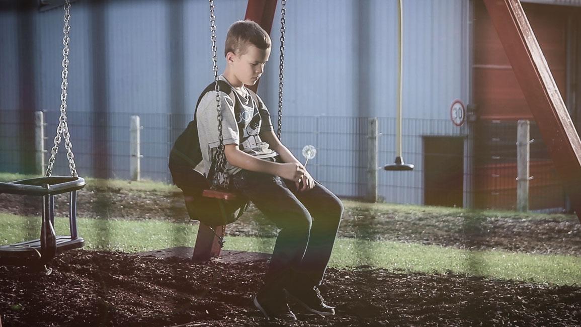 Momentaufnahme der Musikvideo Produktion: Ein Junge sitzt auf der Schaukel eines Spielplatzes. Er betrachtet eine Pustblume, die er in seiner Hand hält