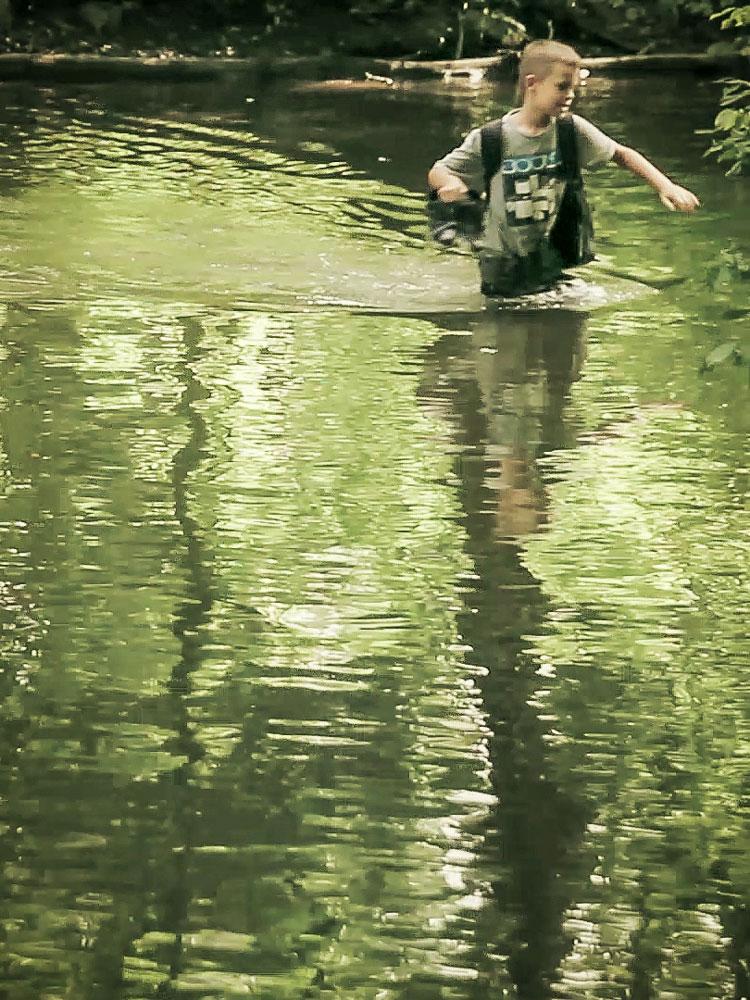 Ein kleiner Junge watet durch einen breiten Fluss - in seiner Hand trägt er seine Schuhe. Was tut man nicht alles für ein Musikvideo