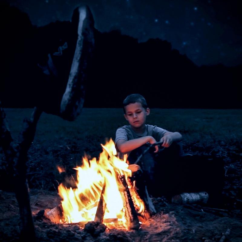 Eine große Wiese mit Waldrand in der Ferne. Ein kleiner Junge sitzt an einem Lagerfeuer - im Vordergrund sind zwei Schuhe zum Trocknen auf einen Stock gesteckt. Für diese Musikvideo Einstellung war viel Compositing nötig