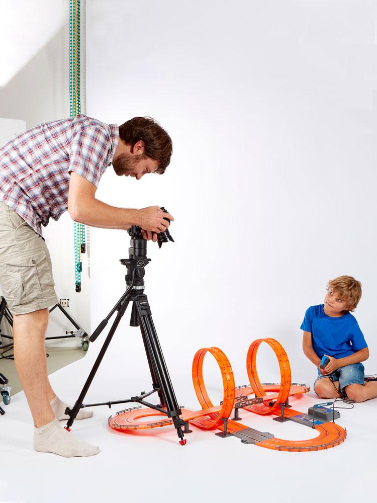 In einem Fotostudio sind zwei Personen auf dem weißen Backdrop, zwischen ihnen eine orangene Rennbahn. Der Mann zur linken bin ich hinter der Kamera - das Produktvideo wird gerade gedreht. Rechts sitzt ein kleiner Junge auf dem Bode, der mit dem Controller in der Hand eines der Autos über die Rennbahn jagd.