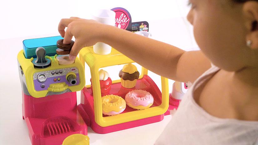 Kamera Blick über die Schulter eines Mädchens auf einen Spielzeug Coffee Shop. Das Mädchen bereitet gerade einen Kaffee zu.