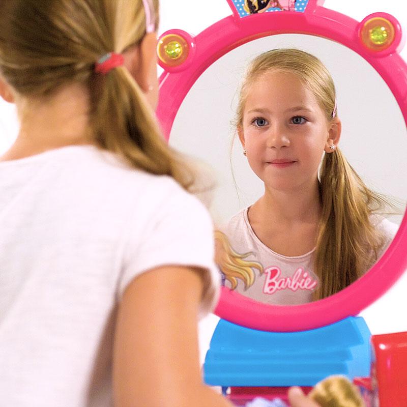 Blick an einem Mädchen mit langen blonden Haaren vorbei auf einem Spiegel, in dem es sich selbst ansieht. Der Spiegel gehört zu einem Schminktisch der in diesem Produktvideo beworben wird.