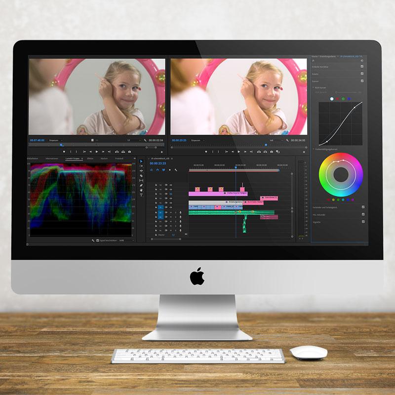 Ein iMac steht auf einem Schreibtisch. Im Videoschnittprogramm Premiere Pro von Adobe werden gerade die Farben bearbietet - zu sehen ist ein kleines Mädchen vorm Barbie Spiegel