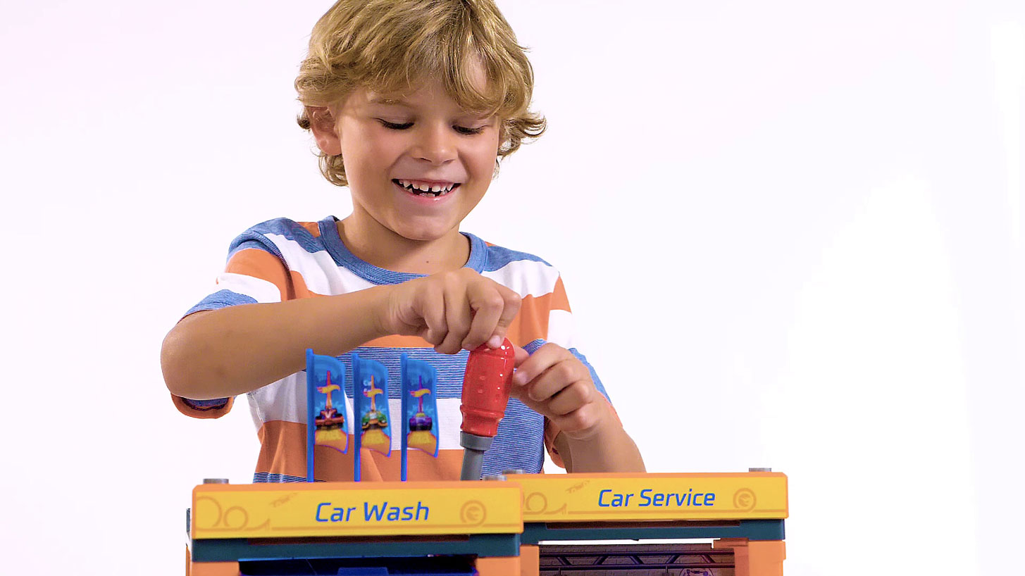 Ein kleiner Junge steht freudig strahlend hinter einer kleinen Spiel Werkstatt, die er mit einem dazugehörigen Schraubenzieher auseinander baut.