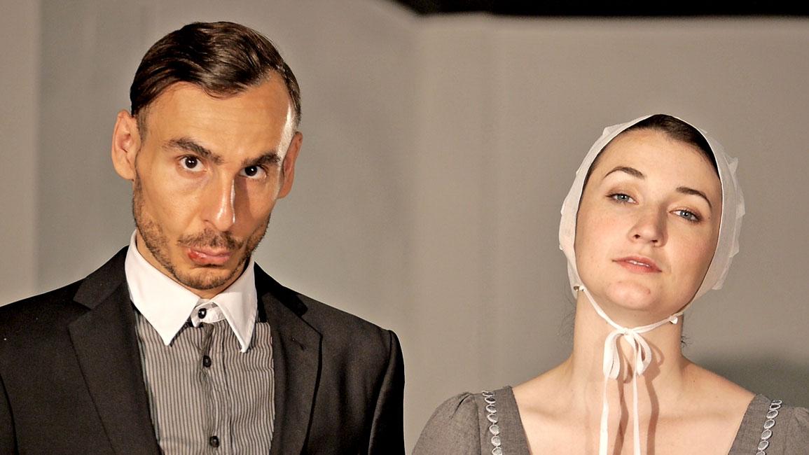 Einstieg in den Theater Trailer: Eine Frau und ein Mann stehen nebeneinander. Beide schauen mit ernstem Blick in die Kamera. Die Kleidung entstammt nicht diesem Jahrhundert.