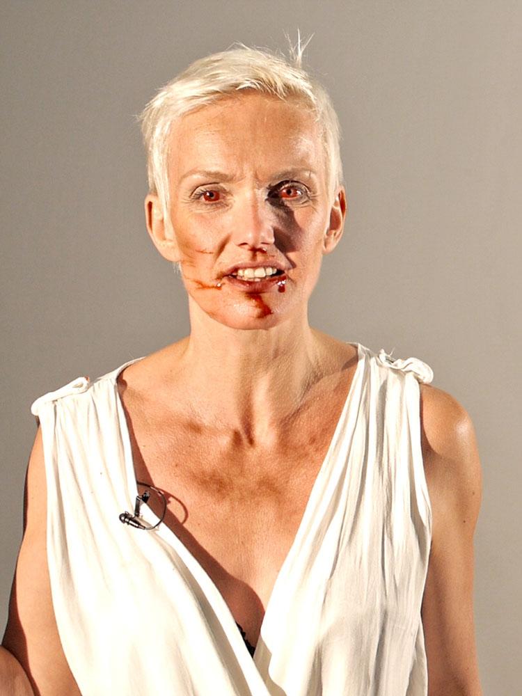 Szene aus der Theaterproduktion: Eine Frau mit roten Kontaktlinsen blickt direkt in die Kamera. Ihr Gesicht ist voller Blut.
