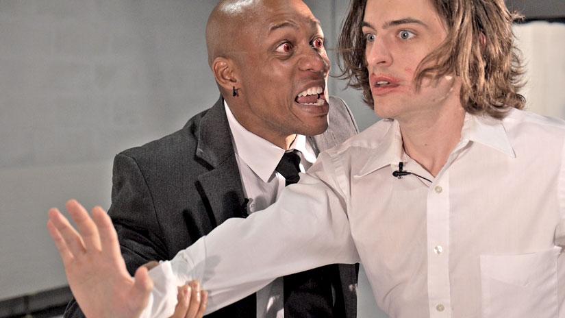 So nahe kommt nur der Trailer bei einer Produktion: Zwei Männer stehen nebeneinander, der linke trägt Kontaktlinsen und scheint den rechten anzuschreiben. Dieser schaut ziemlich verdutzt in die Ferne.