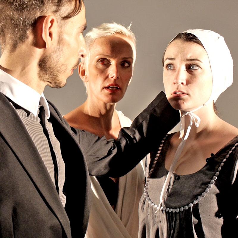 Standbild aus der Theater Trailer Produktion: Zwei Frauen und ein Mann stehen dicht beieinander - sie blicken sich gegenseitig an.