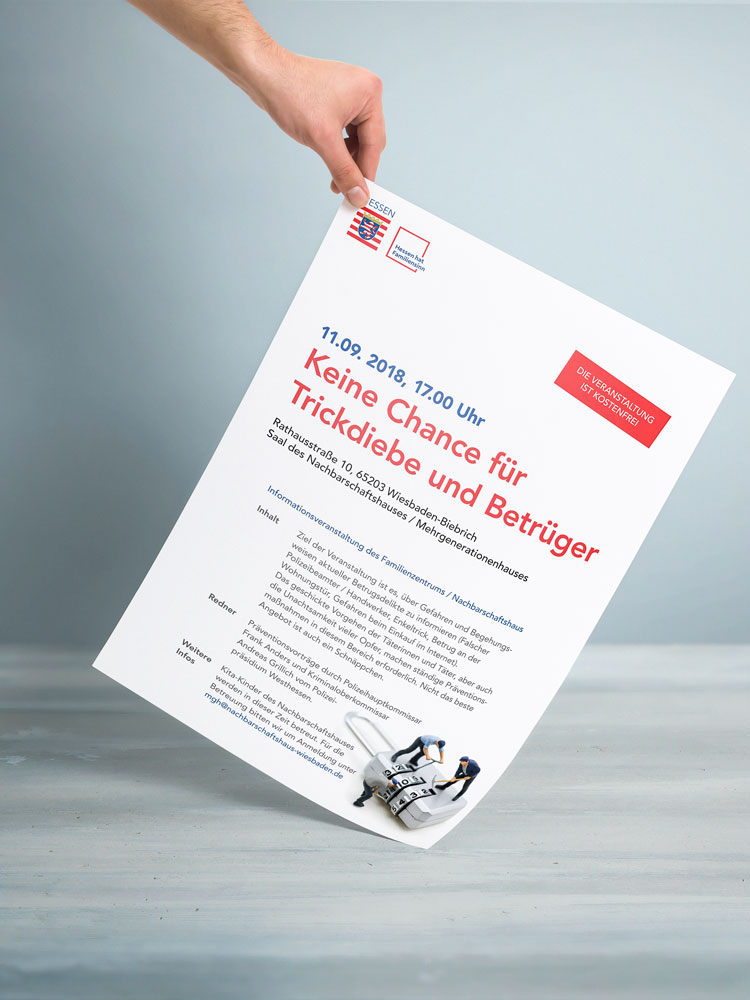 Eine Hand hält eine DinA3 Papier, das frontal zur Kamera nach unten hängt und mit der unteren Ecke auf einem Tisch aufliegt. Auf dem Plakat stehen Informationen zu einer Veranstaltung: