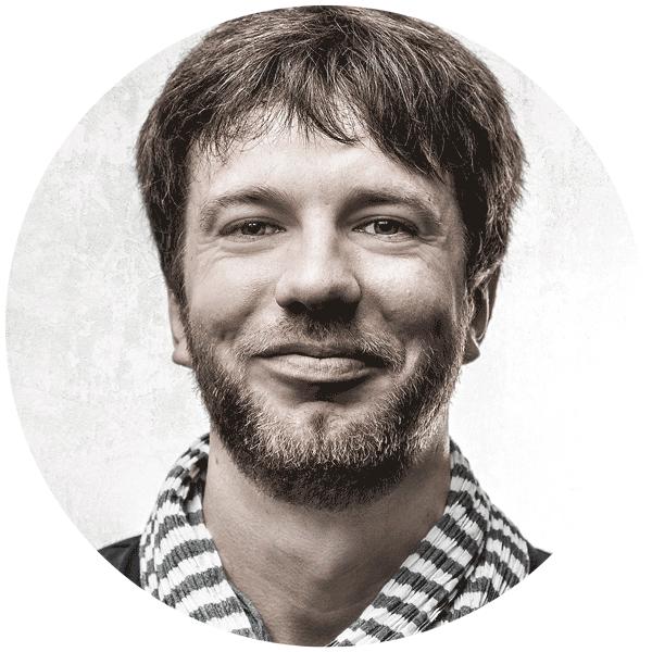 Ein Portraifoto von Florian Thomi, Freelancer für Film, Animation und Print. Frontal in die Kamera schauend und fröhlich grinsend.